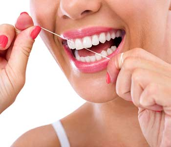 Woman flossing teeth smiling